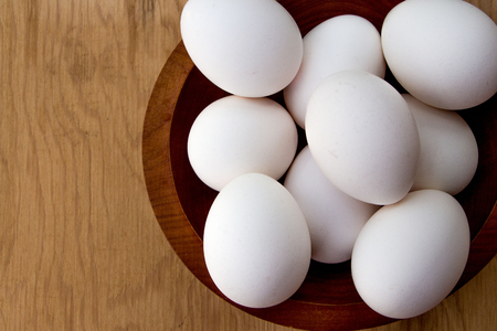 boiled eggs: White eggs in a bowl, wooden background, closeup