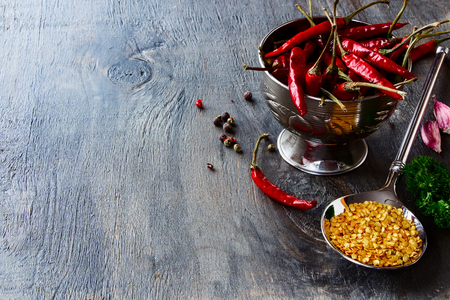 spicy cooking: Hot Chili Peppers with herbs and spices on wooden texture - cooking or spicy food concept