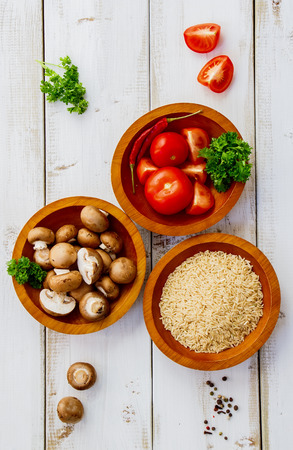 Top view of cooking background with raw rice, mushrooms, tomatoes, herbs and spices over white wooden board