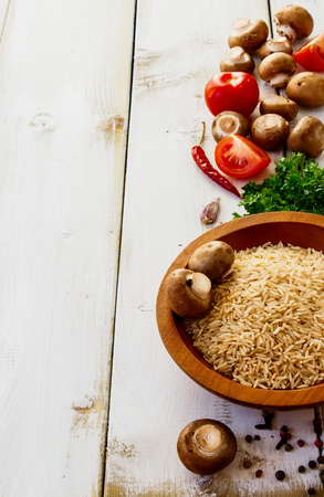 Ingredients rice, mushrooms, tomatoes, herbs and spices for cooking over white wooden background Stock Photo