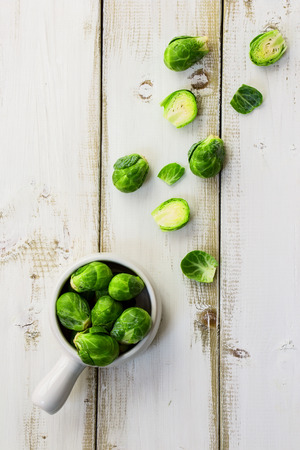 Fresh brussel sprouts over white wooden background. Top view