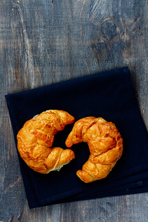 Fresh Croissants on wooden rustic background. Top view. Food and breakfast concept.