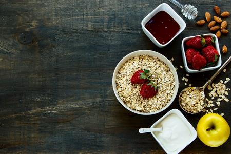 健康的な朝食。ミューズリーと素朴な木製の背景上果実ヨーグルト。健康やダイエットのコンセプトです。平面図です。 写真素材