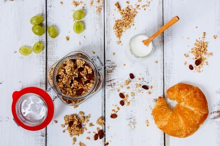 yogurt: Granola, muesli, yogurt, grape, fresh berries and croissant for healthy breakfast.on white wooden background. Health and diet concept. Top view.
