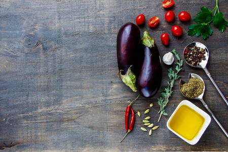 Fresh eggplants with aromatic herbs, spices and vegetables on a Wooden Background. Vegetarian food, health or cooking concept.