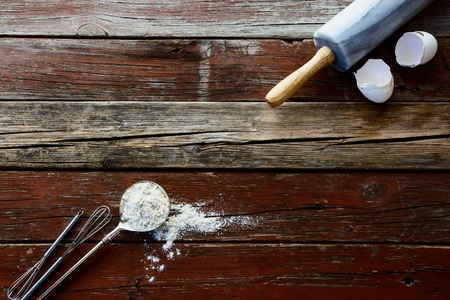 Top view of baking background with eggshell and rolling pin. Wood background. Stock Photo