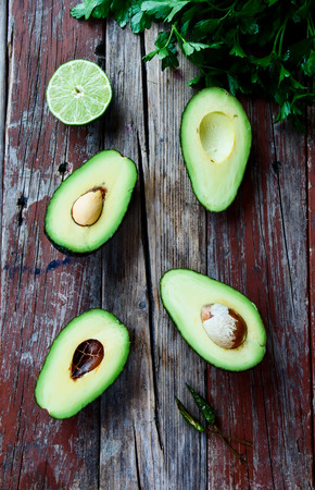 rustic food: Fresh, green avocado, lime and parsley on rustic wooden background - healthy food, diet or cooking concept. Top view.