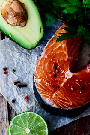Delicious salmon steak, avocado, lime and parsley over old wooden texture - healthy food, diet or cooking concept. Top view.