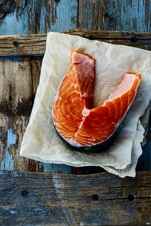 dog salmon: Top view of raw salmon steak on rustic wooden background.