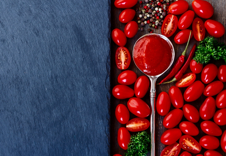 Food background with tomato sauce, tomatoes and spices. Slate and wood background with copyspace. Top view.