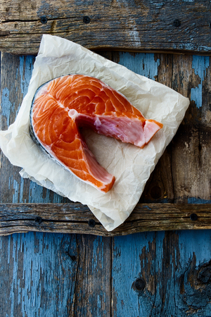 dog salmon: Raw, fresh salmon steak on rustic wooden background. Top view. Stock Photo