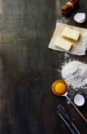 クッキー材料 - 小麦粉、砂糖、卵、バター ヴィンテージの木製テーブルの上。平面図です。フリー テキスト スペースを持つ素朴な背景は。 写真素材