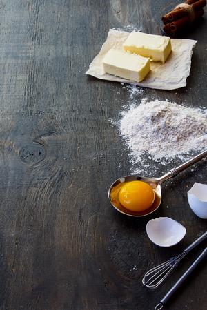 材料の小麦粉、砂糖、卵を焼くヴィンテージの木製テーブルにバター。フリー テキスト スペースを持つ素朴な背景は。