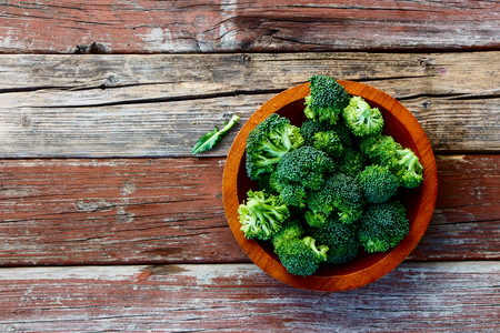 Fresh green broccoli in wood bowl over rustic wooden background - healthy or vegetarian food concept  Top view. Banco de Imagens