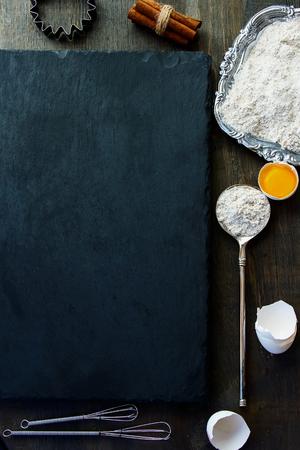 未加工卵、卵殻、シナモン、小麦粉を背景を焼きます。平面図です。スレートと木材の背景。Copyspace がたくさん。