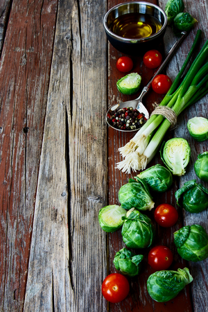 Bruxelles: Fresh green Bruxelles sprouts and Healthy Organic Vegetables on a Wooden Background.