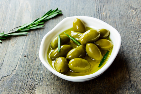 olive green: bowl of fresh green olives in olive oil on a rustic wooden texture, selective focus