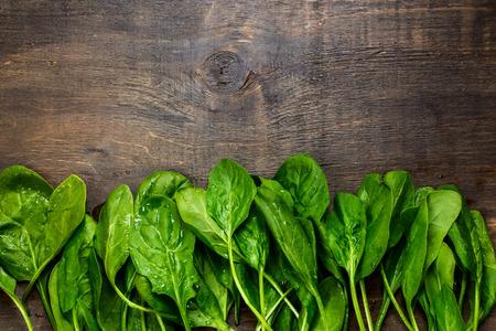 verse groene spinazie op uitstekende houten textuur, bovenaanzicht