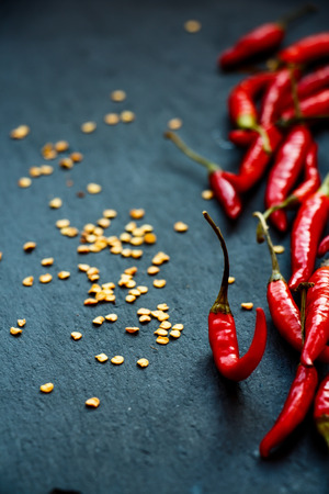 Hot Red Chili Peppers over dark grey background. Selective focus.