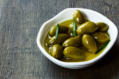olive green: whole fresh green olives in a bowl of olive oil on a rustic wooden tabletop, selective focus
