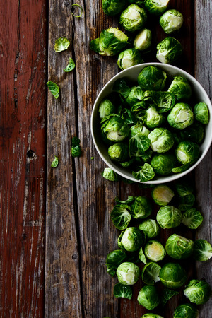 sprout: Top view of organic brussel sprouts in a white bowl on rustic wooden table. Stock Photo