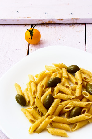 typical: Penne pasta with pesto, olives and tomatoes on white wooden background.