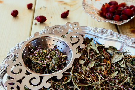 tea party: Mix of bio herbal tea and hip roses on wooden background. Stock Photo
