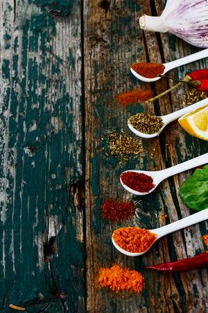 hierbas: Especias y hierbas surtido en las cucharas sobre fondo de madera. Comida vegetariana, la salud o el concepto de cocina. Enfoque selectivo. Foto de archivo