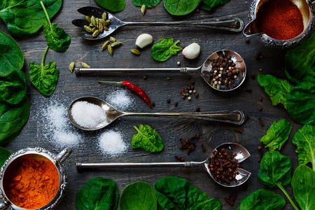 potherb: Food Elements - Herbs and spices selection, old metal spoons and dark wood - cooking, healthy eating. Top view.