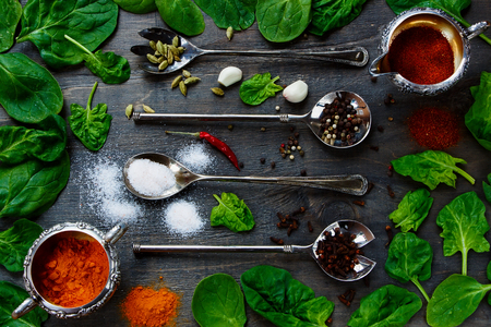 potherb: Food Elements - Herbs and spices selection, vintage metal spoons and old dark wood - cooking, healthy eating. Top view.
