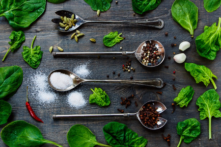 potherb: Herbs and spices in old metal spoons on rustic wooden background Stock Photo