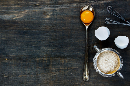 Food background with copy space - egg yolk in vintage spoon and flour in vintage cup on wooden texture. Top view.