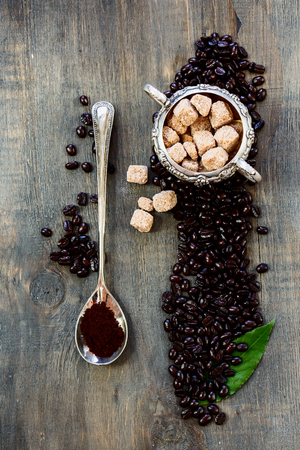 coffeetree: Top view of composition with coffee in vintage spoon and sugar on dark wooden background.