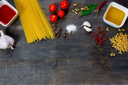 Pasta and ingredients on dark wooden background with copy space. Top view.