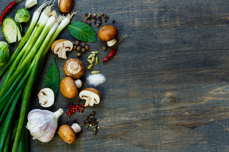 Top view of fresh mushrooms and ingredients on dark wooden table. Background with space for text