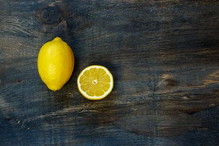 暗い素朴なボード上のレモンを半分にカットし、全体の平面図です。テキストのためのスペースとの背景。 写真素材
