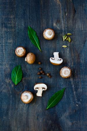 epices: Vue de dessus de champignons frais avec des épices et des herbes sur fond de bois sombre.