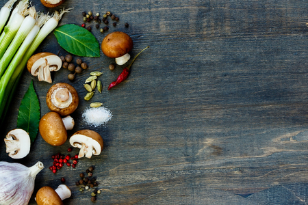 Fresh mushrooms and ingredients on dark wooden background