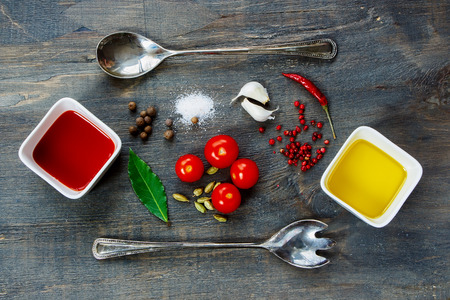 make a paste: Food background with sauce ingredients (tomato, olive oil, garlic, salt and pepper) on dark wooden texture. Vegetarian food, health or cooking concept. Top view. Stock Photo