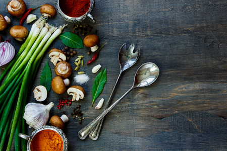 暗い木製のテーブルの上の野菜とスパイスの新鮮なキノコの平面図です。テキストのためのスペースとの背景。ベジタリアン料理、健康、料理の概 写真素材
