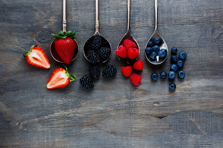 Top view of berries mixed (strawberries, raspberries, blueberries and blackberries) on vintage metal spoons over dark wooden board. Agriculture, Gardening, Harvest Concept. Background with space for text. Zdjęcie Seryjne