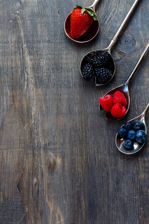 Berries mixed on vintage metal spoons over dark wooden board. Agriculture, Gardening, Harvest Concept. Background with space for text. Stock Photo