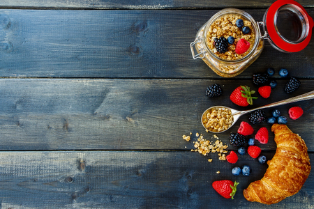 Top view of homemade granola in glass jar, fresh berries and croissant for breakfast on dark wooden table. Health and diet concept. Background with space for text. Stock Photo