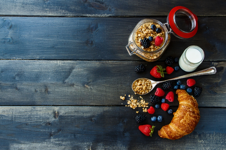 crunchy: Croissant, fresh berries, yogurt and homemade granola in glass jar for breakfast on dark wooden table. Health and diet concept. Background with space for text. Stock Photo
