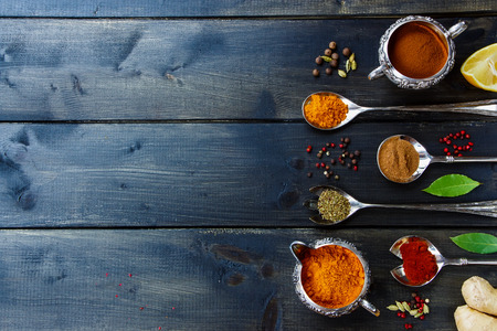 古い金属製のカップとスプーン暗い木製のテーブルの上で様々 な粉末のスパイス。テキストのためのスペースとの背景。食べ物や料理の概念。平面