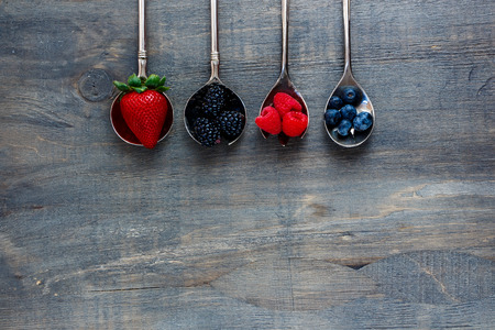 wooden spoon: Tasty fresh berries (strawberries, raspberries, blueberries and blackberries) on vintage metal spoons over dark wooden board. Agriculture, Gardening, Harvest Concept. Background with space for text. Stock Photo
