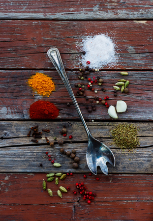 potherb: Vintage metal spoon and spices selection on rustic wooden background. Cooking, vegetarian food or health concept. Stock Photo