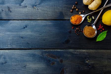 Bovenaanzicht van verschillende kruiden en specerijen selectie op donkere houten tafel. Achtergrond met ruimte voor tekst.