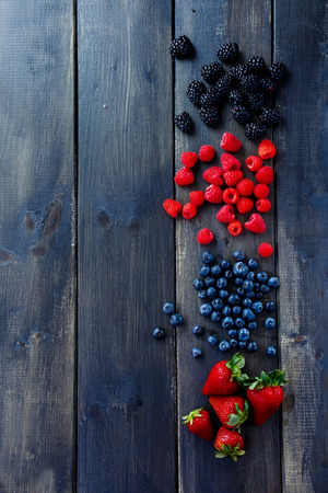 Houten achtergrond met organische lente of zomer bessen (aardbeien, frambozen, bosbessen en braambessen). Landbouw, tuinieren, oogstconcept. Bovenaanzicht. Ruimte voor tekst. Stockfoto