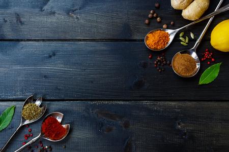 暗い木製のテーブルにハーブやスパイスを用いて背景。食べ物や料理の概念。平面図です。